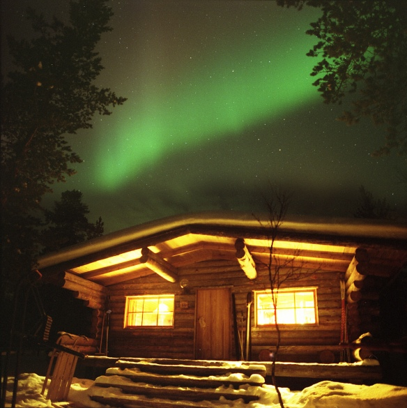 A Mamiya 7 photograph of northern lights aurora over a log cabin in lapland
