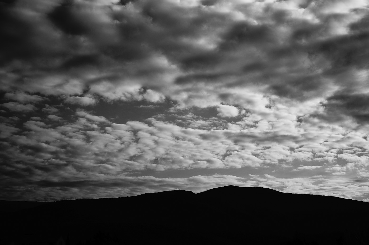 Clouds over a distant hill in black and white, picture made with a Sony NEX-5N