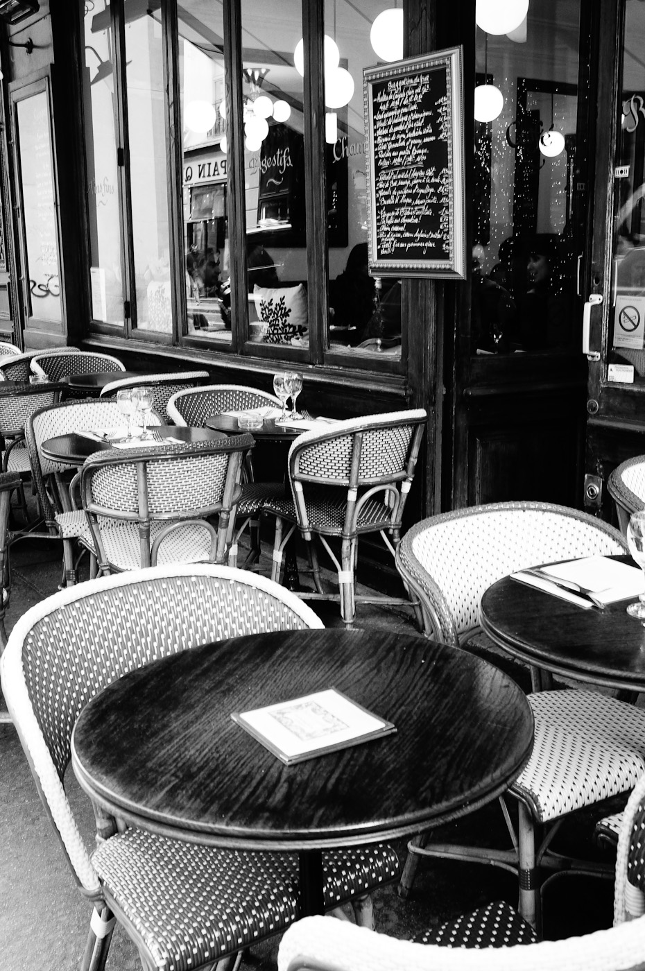 Tables and chairs in front of a parisian caffe