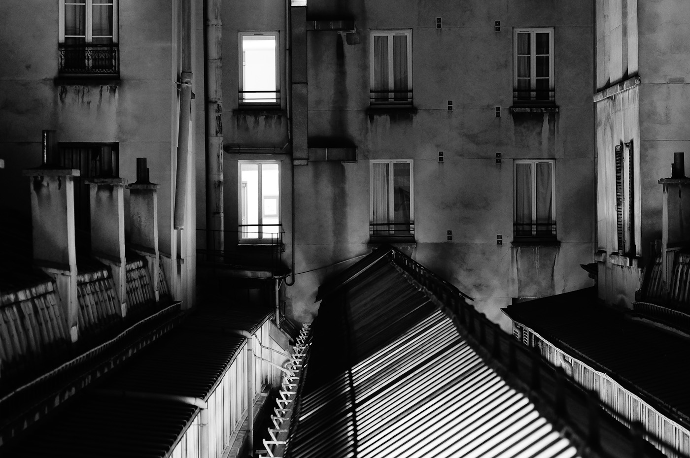 A view across a glass roof passage way to houses in Paris