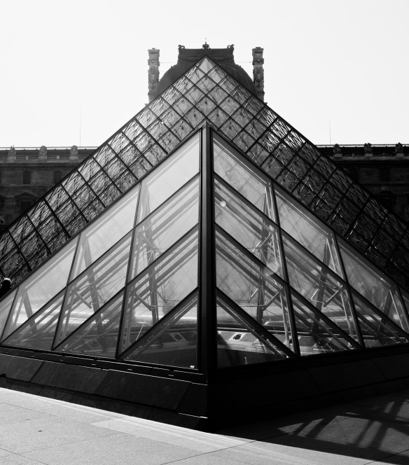 A small glass pyramid in front of a larger one, against the background of the Louvre Museum in Paris. Sony NEX-5N and Zeiss ZM Biogon 25mm f/2.8
