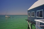 The blue Busselton Jetty interpretive center agains the gree sea and a sail boat under the sun