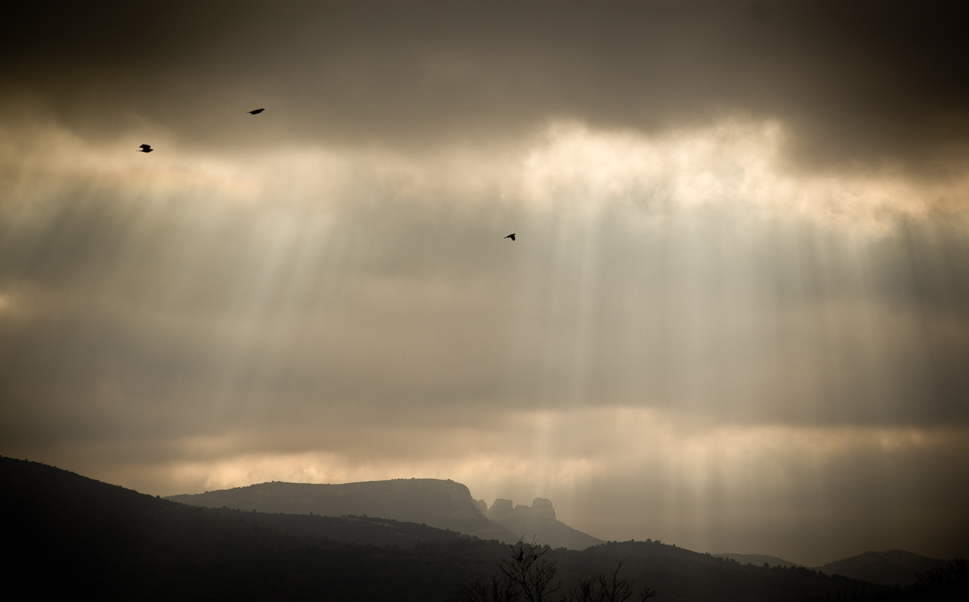 Sun rays beneath dark clouds streak the saky and the hills of Provence. Sony NEX-5n and Leica M Elmarit 90mm f/2.8