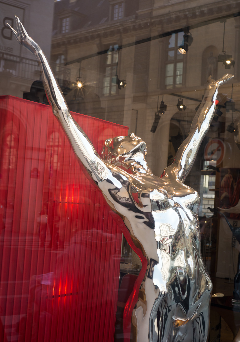 A silver statue of a naked woman facing the sky with her arms reaching up. Sony NEX-5n and Zeiss ZM 25/2.8