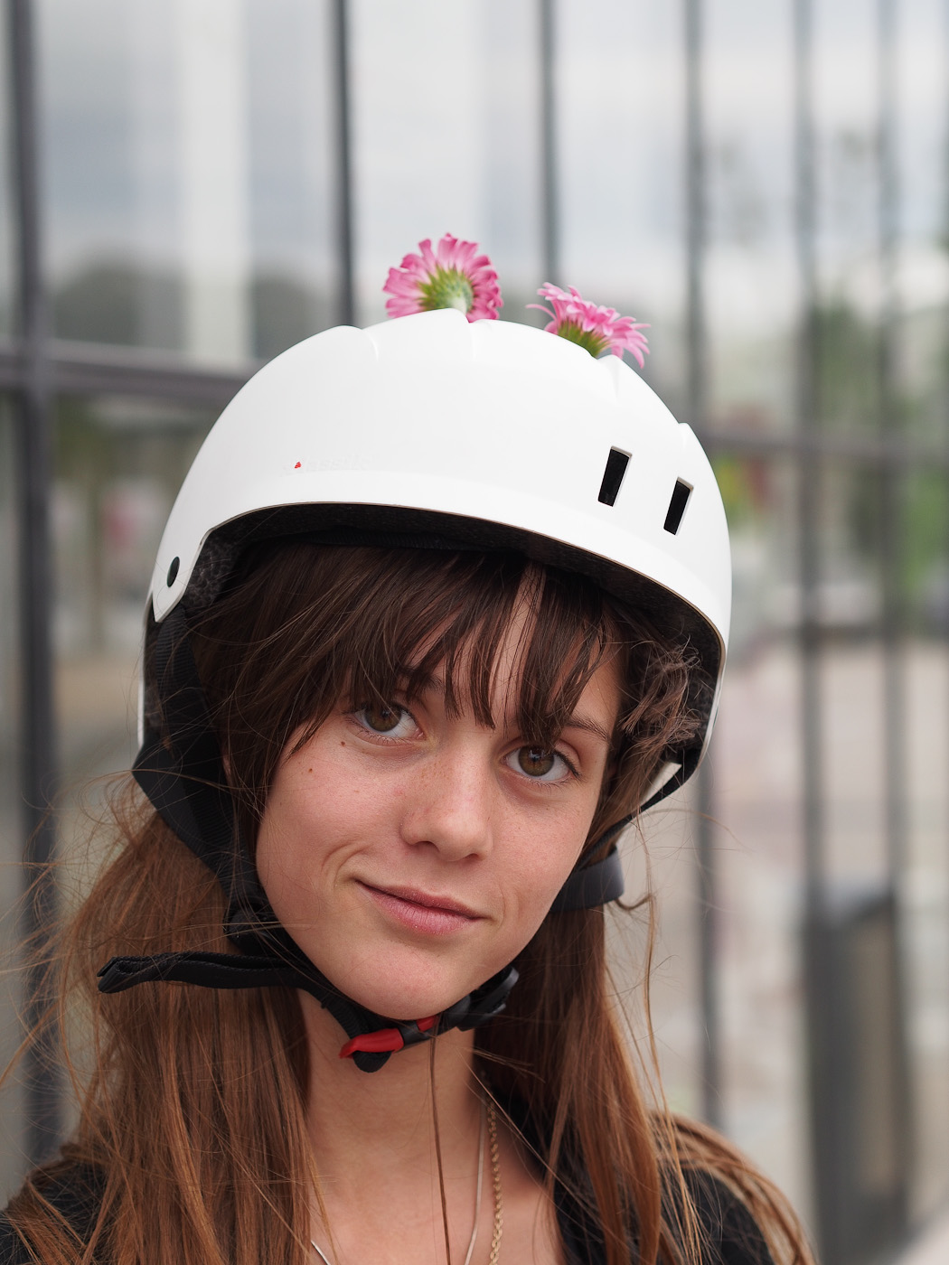 A young rollerskater girl has flowers sticking out of her helmet. Olympus OM-D E-M5 & Olympus Digital Zuiko 45mm f1.8