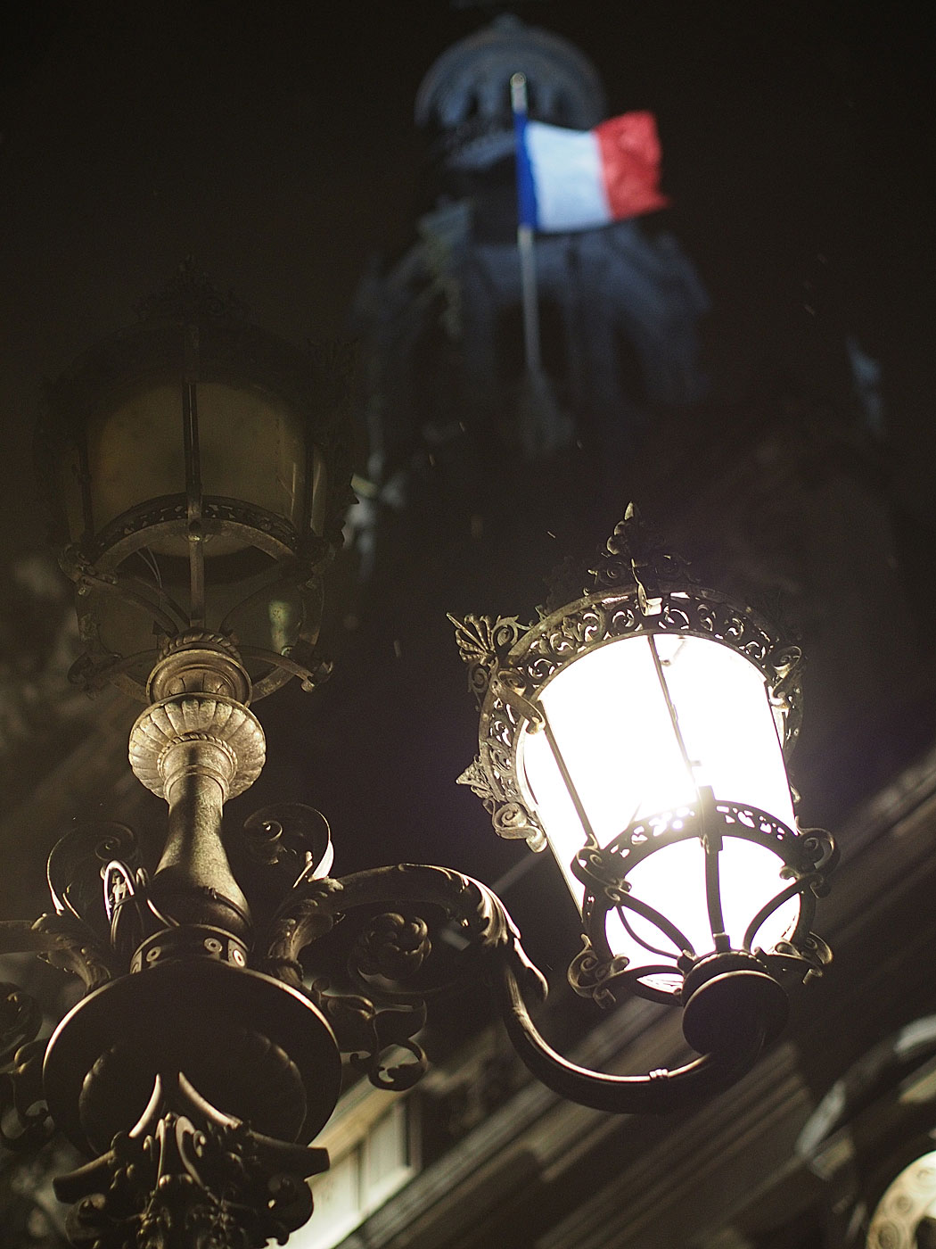The French national flag floats over the Hotel de Ville and its lamp posts in Paris. Olympus OM-D & Digital Zuiko 45mm f/1.8