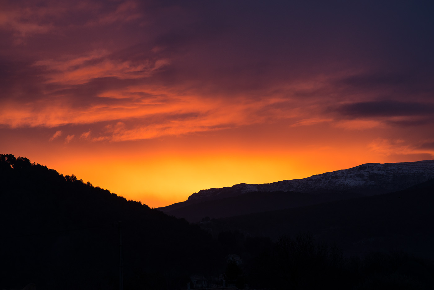 A red sunrise over the hills of provence on a snowy winter day