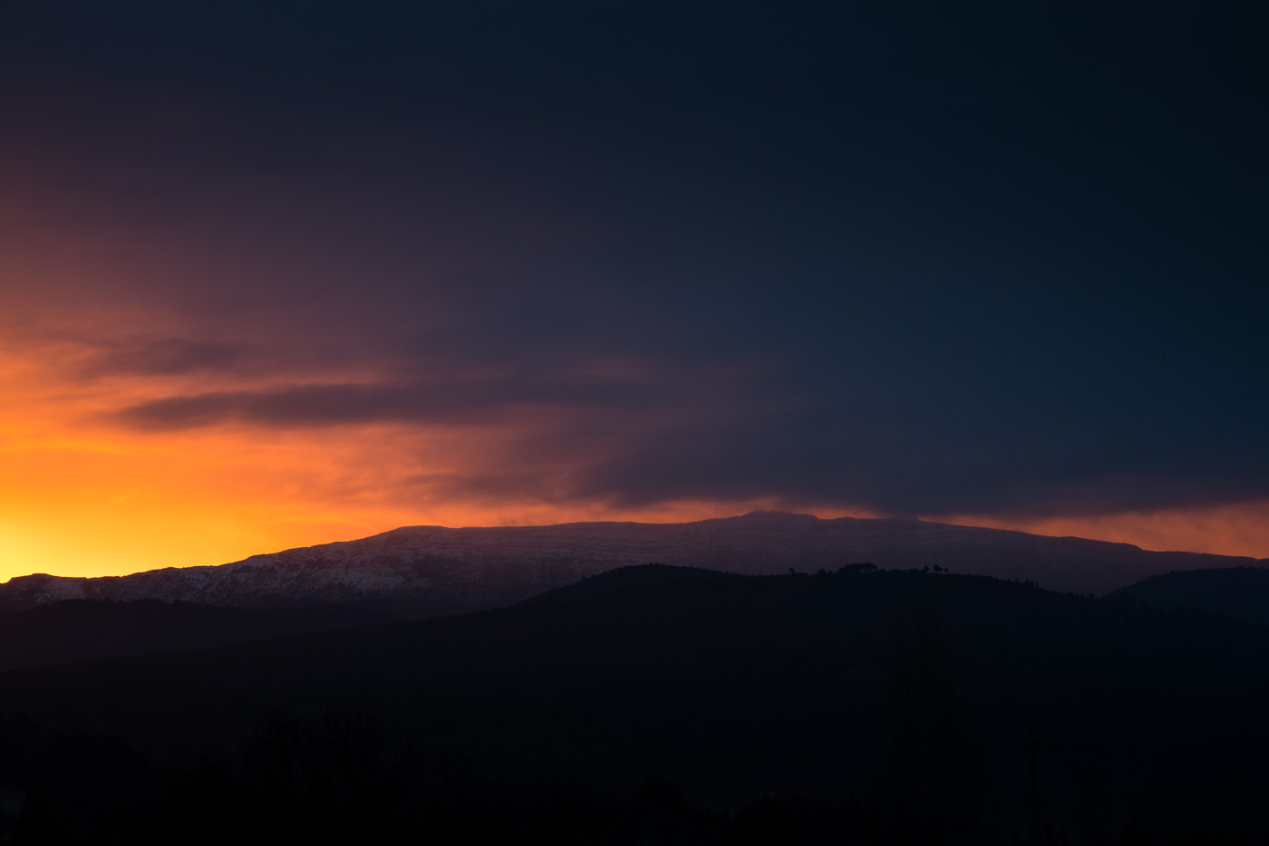 A triangle of orange light formw over the hills of provence on a snowy morning. Nikon D800e & Leica Elmarit-R 90/2.8