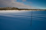 A stick in the snow marks a path on a Lapland frozen laike. Nikon D800e & Leica-R 50 Summicron