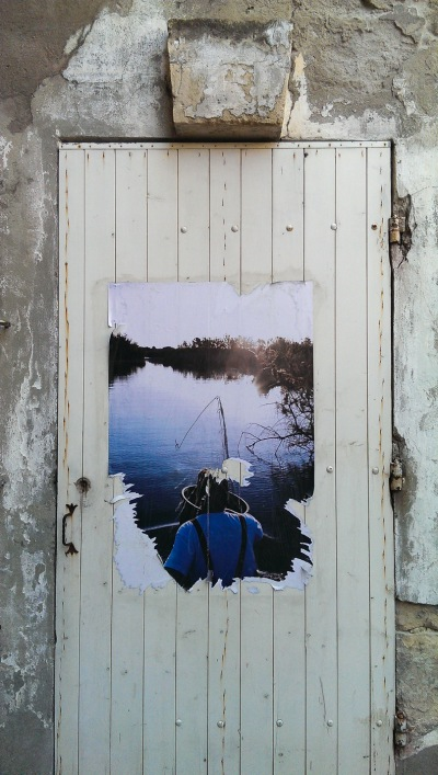 A poster of a fisherman on an old door in Arles. Part of a review of the HTC One camera