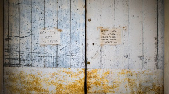 Two handwritten sign posts on a garage door in Provence asking people to stop their dogs pooing in front of the garage. Nikon D800. Humorous